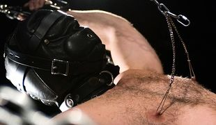 Mr. Kristofer, strapped into a sensory deprivation hood, is escorted to the bondage sling where Sir teases the head of his cock