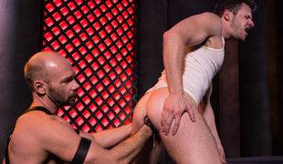 Brian Bonds, clad in white briefs and a white tank, makes out with Mike Tanner, who wears a kinky ebony leather harness with matching jockstrap